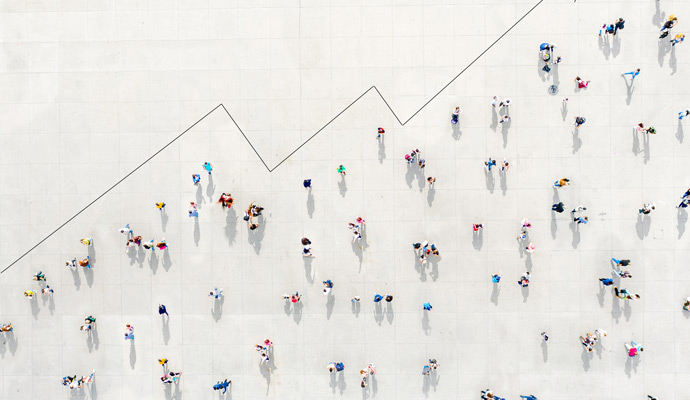 An overhead view of a crowd of people forms the shape of an ascending growth chart.