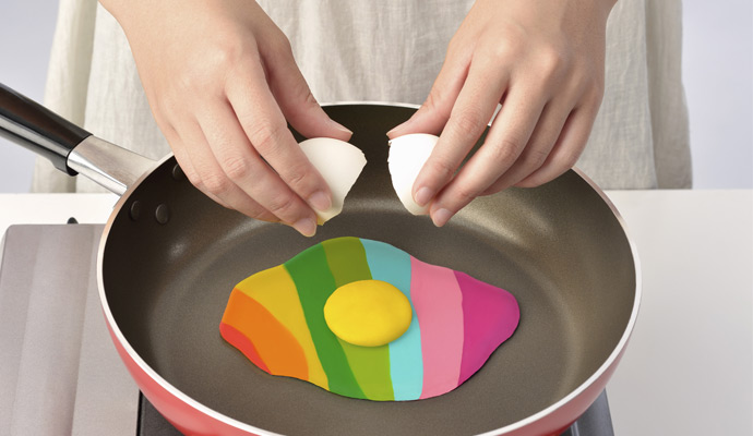 A chef cracks an egg into a frying pan, revealing an unexpected rainbow of colors.