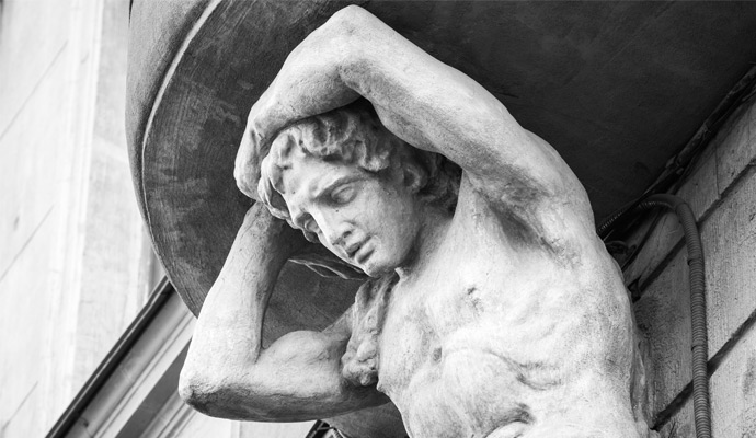 A photo of a sculpture of Atlas on the facade of an old house.