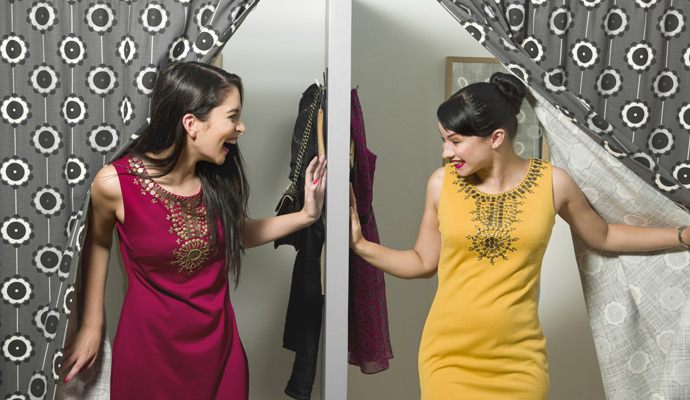 Two women emerge from neighboring fitting rooms and happily discover they are wearing the same dress