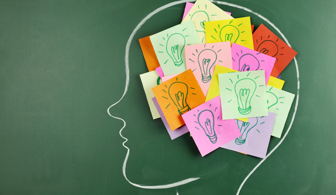 A chalkboard outline of a person's head is filled with Post-it notes, with drawings of light bulbs visible on each note.