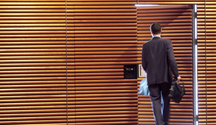 A businessman is seen from behind as he exits the door of a wood-paneled office.