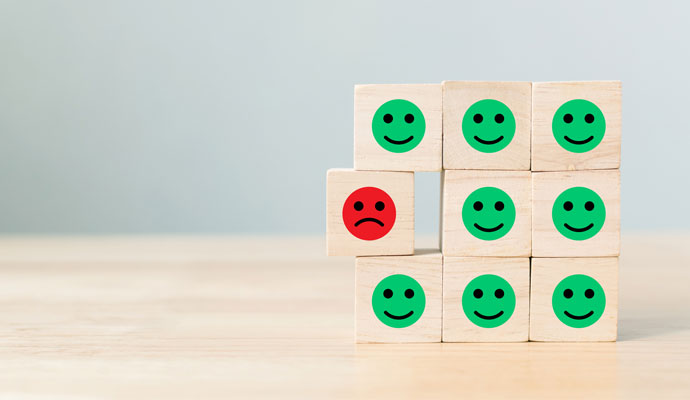 Wooden blocks with cartoon face icons, most of them are smiling, one is frowning