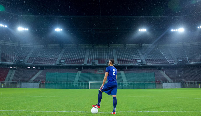 Soccer player standing in an empty stadium