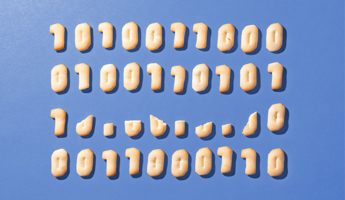 A grid of cookies — including some that are crumbled and broken — baked in the shape of binary code ones and zeros, against a blue background.