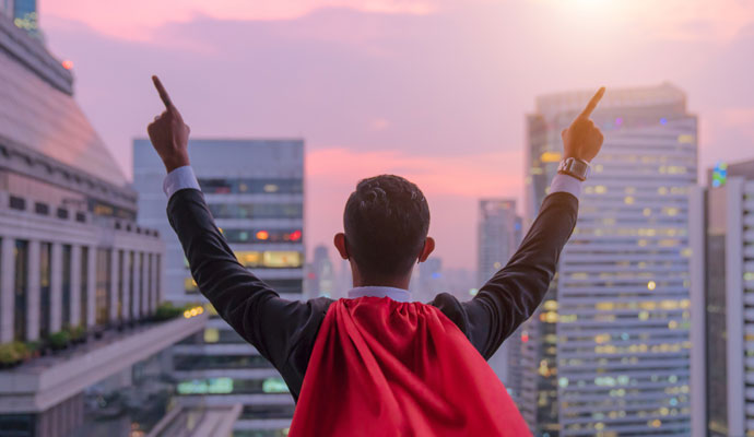Superhero businessman looking at city skyline at sunset, arms raised in victory