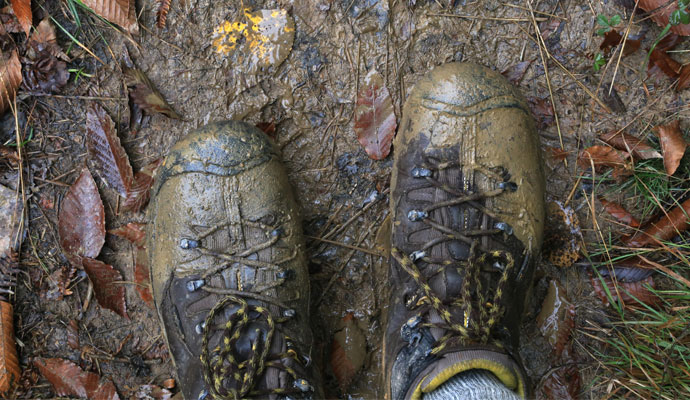 An overhead view focuses on a hiker's pair of mud-covered boots, with leaves, grass, and mud scattered on the trail beneath them.