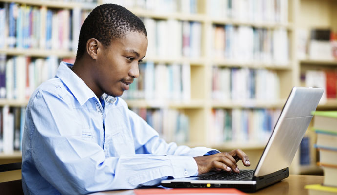 Young man works on a laptop in a library