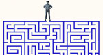 A woman stands atop a blue maze, peering down into its entrance.