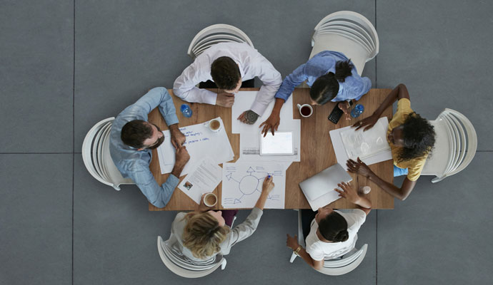 An overhead view of a group of businesspeople gathered around a table for a lively, engaging meeting.