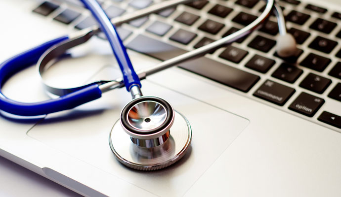 A stethoscope rests upon a laptop keyboard.