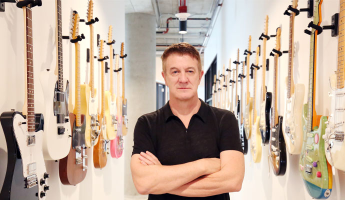 Fender CEO Andy Mooney pauses in a hallway lined with guitars.