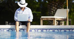 A businessman with a drink and a laptop dangles his feet into a swimming pool.