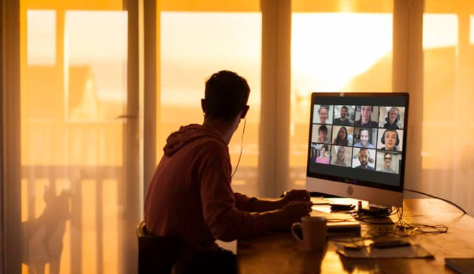 A photograph of a man, who is working from home, participating in a video conference call.