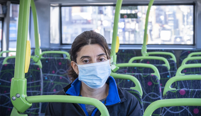 A woman in a surgical mask riding a city bus