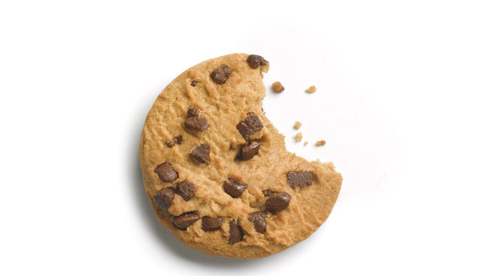 Close-up of a chocolate chip cookie with a bite taken out of it, on a white background.