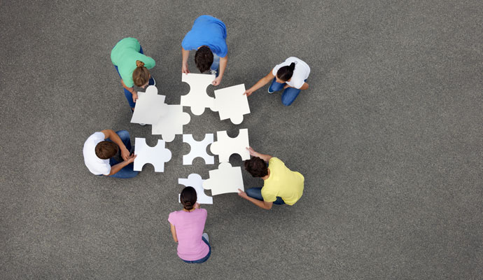 Six people seen from above, putting together giant jigsaw puzzle pieces