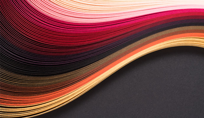 A stack of pink, red, brown, orange, and yellow paper curls in the shape of a wave against a black background.