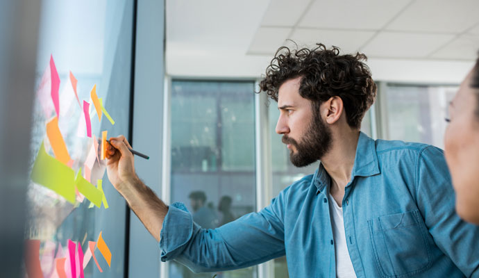 A young worker organizes his ideas by posting sticky notes on a window.