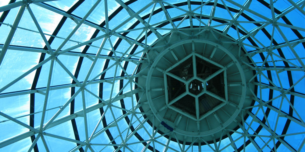 A glass architectural dome, seen from underneath, with a hexagon at its center