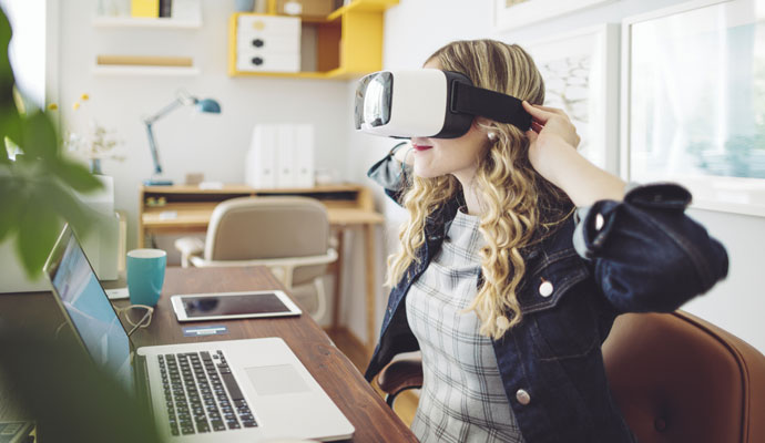A woman adjusts her virtual reality headset and prepares to work from home.