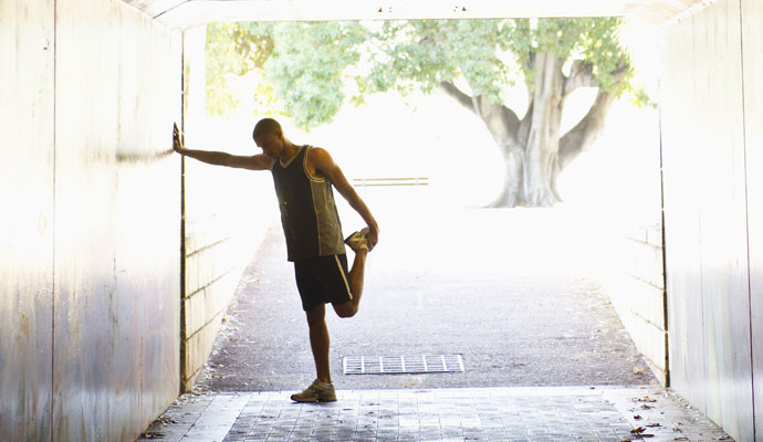A man stretches his left leg before going on a run. He's standing at the end of a tunnel, and a leafy tree and a sunny day can be seen beyond the tunnel.
