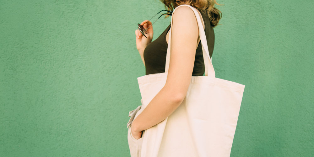 A photo of a woman standing in profile against a green wall, with a cream-colored canvas shopping bag over her shoulder.