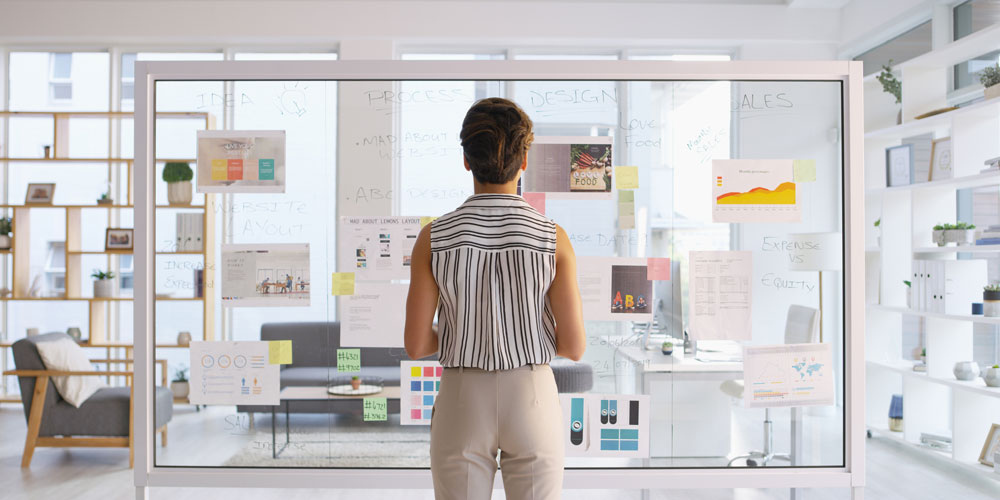 A businesswoman considers the options arrayed before her on a glass office wall.